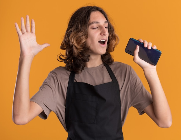Joyful young handsome barber wearing uniform keeping hand in air holding mobile phone using it as microphone singing with closed eyes isolated on orange wall