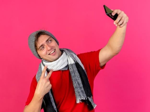 冬の帽子と真っ赤な壁に隔離されたselfieを取るピースサインをしているスカーフを身に着けているうれしそうな若いハンサムな金髪の病気の男