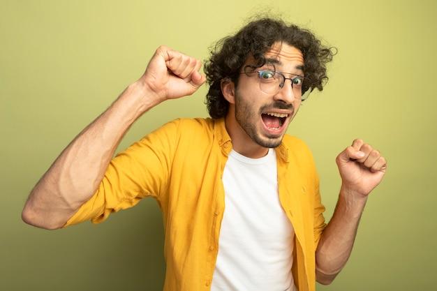 オリーブグリーンの壁に分離されたはいジェスチャーを行う眼鏡をかけているうれしそうな若いハンサムな白人男性