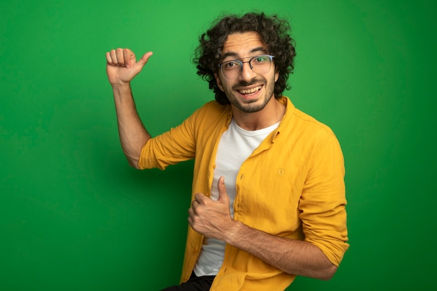 Gioioso giovane uomo caucasico bello con gli occhiali che mostra i pollici in su isolato sulla parete verde con lo spazio della copia