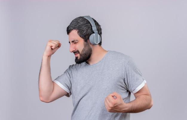 Gioioso giovane uomo caucasico bello che indossa le cuffie che ascolta la musica con i pugni chiusi e gli occhi chiusi isolati su bianco