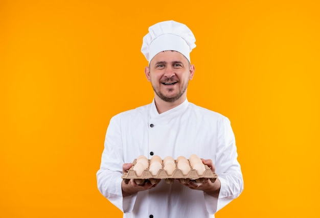 Joyful young handsome cook in chef uniform holding carton of eggs isolated on orange wall