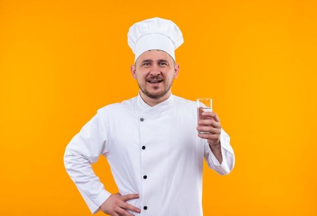Gioioso giovane e bello cuoco in uniforme da chef che tiene in mano un bicchiere d'acqua isolato su una parete arancione
