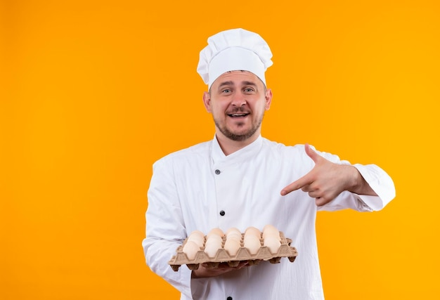 Joyful young handsome cook in chef uniform holding and pointing at carton of eggs isolated on orange wall