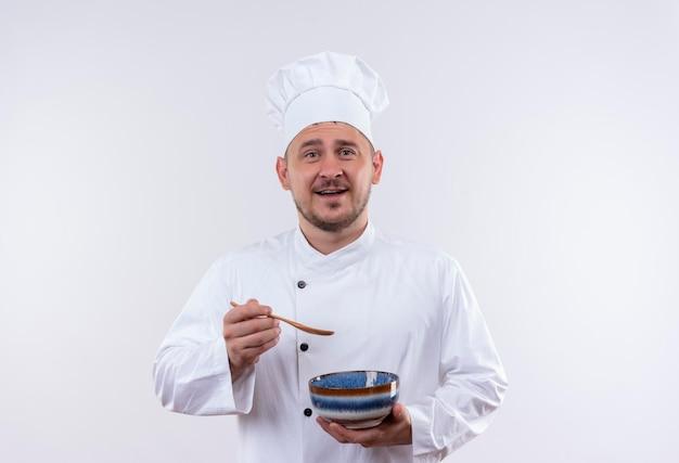 コピー スペースを持つ孤立した白い壁にボウルとスプーンを保持しているシェフの制服を着たうれしそうな若いハンサムな料理人