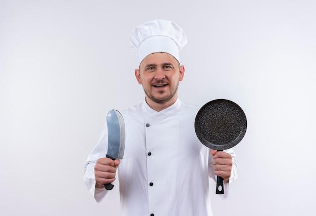 コピー スペースを持つ孤立した白い壁に包丁とフライパンを保持しているシェフの制服を着たうれしそうな若いハンサムな料理人