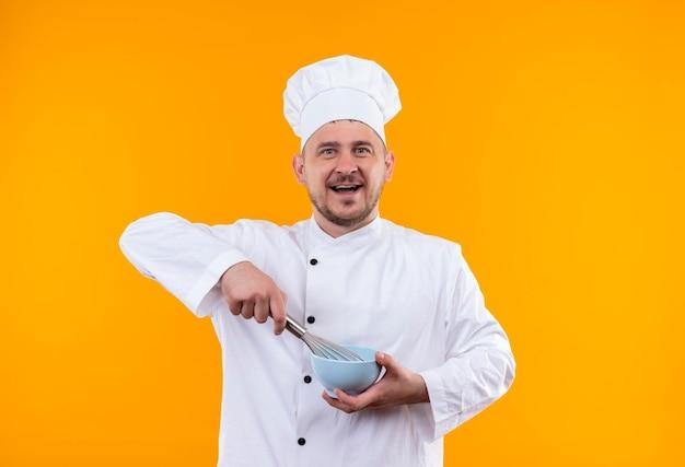 オレンジ色の壁に分離された泡立て器とボウルを保持しているシェフの制服を着たうれしそうな若いハンサムな料理人