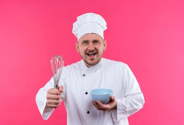 ピンクの壁に泡立て器とボウルを保持しているシェフの制服を着たうれしそうな若いハンサムな料理人 無料写真