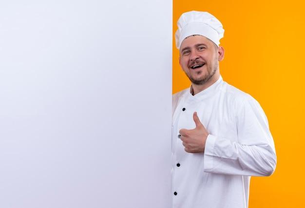 シェフの制服を着たうれしそうな若いハンサムな料理人が白い壁の後ろに立ち、コピースペースのあるオレンジ色の壁に分離された親指を現す