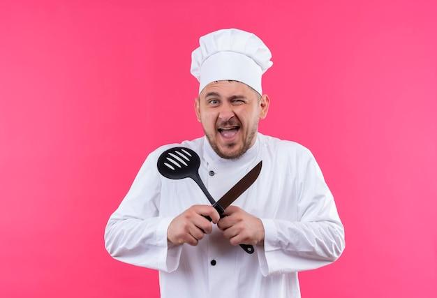 シェフの制服を着たうれしそうな若いハンサムな料理人がまばたきし、ピンクの壁にスロット付きのスプーンとナイフを保持