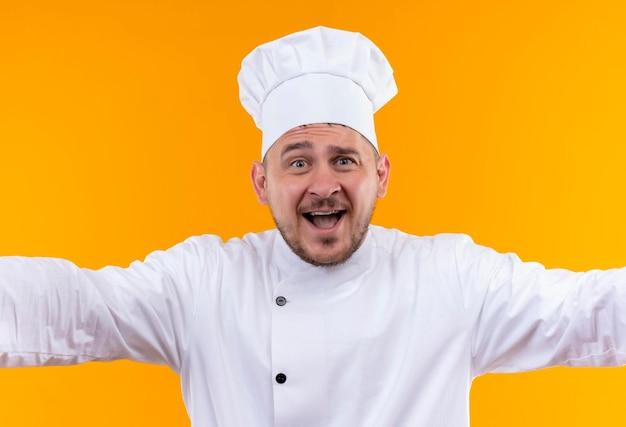오렌지 벽에 고립 된 두 팔을 벌려 요리사 유니폼에 즐거운 젊은 잘 생긴 요리사