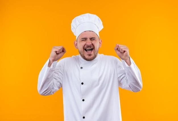 孤立したオレンジ色の壁に拳を上げ、目を閉じたシェフの制服を着たうれしそうな若いハンサムな料理人