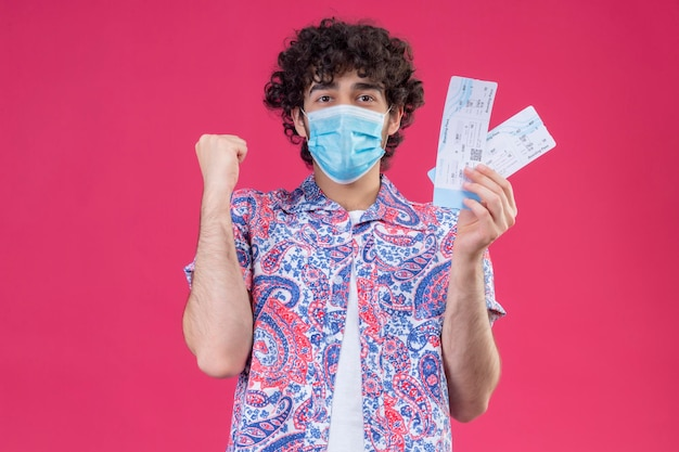 コピースペースと孤立したピンクのスペースに上げられた握りこぶしで飛行機のチケットを保持している医療マスクを身に着けているうれしそうな若いハンサムな巻き毛の旅行者