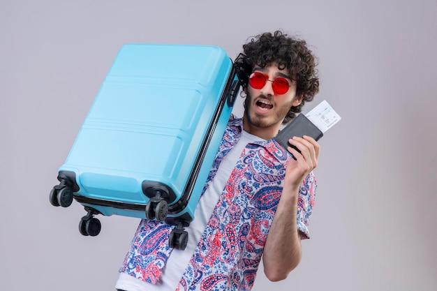コピースペースと隔離された白いスペースに飛行機のチケット、財布、スーツケースを保持しているサングラスを身に着けているうれしそうな若いハンサムな巻き毛の旅行者の男