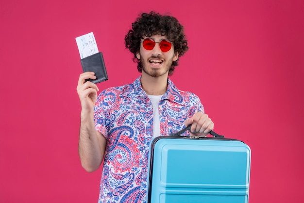 Joyful young handsome curly traveler man wearing sunglasses holding wallet and airplane tickets with suitcase on isolated pink space with copy space