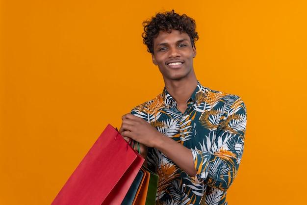Радостный молодой красивый темнокожий мужчина с вьющимися волосами в рубашке с принтом листьев улыбается, держа сумки для покупок, стоя на оранжевом фоне