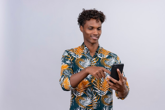 Joyful young handsome dark-skinned man with curly hair in leaves printed shirt holding smartphone hands and touching screen of mobile phone on a white background