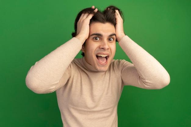 즐거운 젊은 잘 생긴 남자가 녹색 벽에 고립 된 머리를 잡고