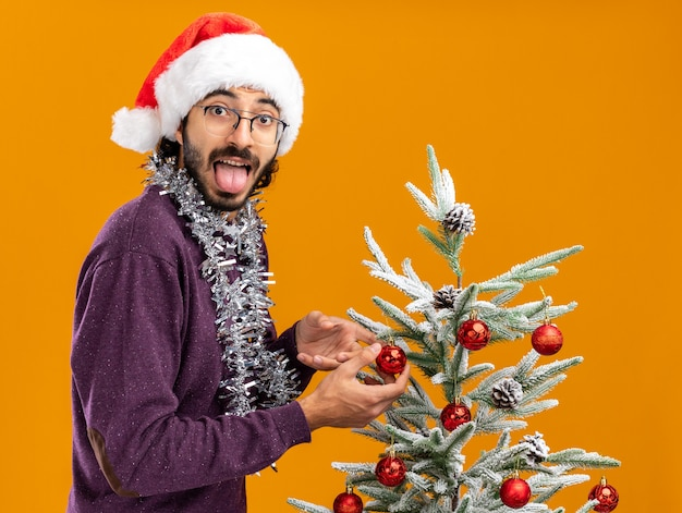 Joyful young handsome guy standing nearby christmas tree wearing christmas hat with garland on neck showing tongue isolated on orange background