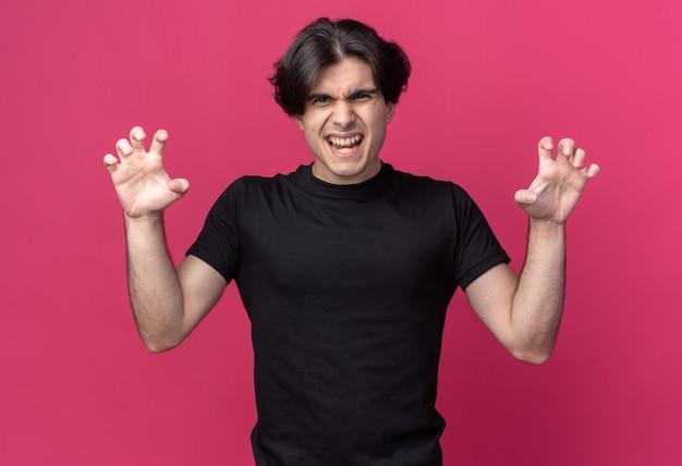 분홍색 벽에 고립 된 호랑이 스타일 제스처를 하 고 검은 티셔츠를 입고 즐거운 젊은 잘 생긴 남자