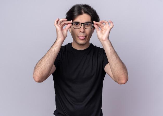 Радостный молодой красивый парень в черной футболке, носящий и держащий очки, показывает язык, изолированный на белой стене
