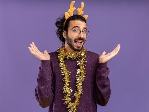 青い背景で隔離の手を広げて首に花輪とクリスマスの髪のフープを身に着けているうれしそうな若いハンサムな男
