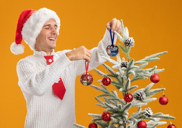Joyful young handsome guy wearing christmas hat and santa claus tie standing near christmas tree decorating it with christmas ball ornaments isolated on orange background