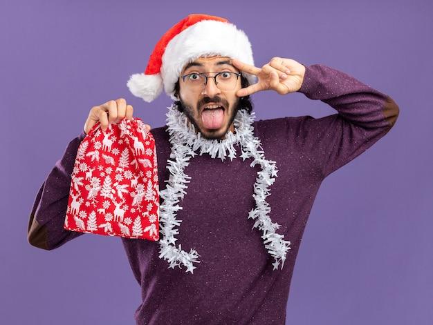 青い背景で隔離の舌と平和のジェスチャーを示すクリスマスバッグを保持している首に花輪とクリスマスの帽子をかぶってうれしそうな若いハンサムな男