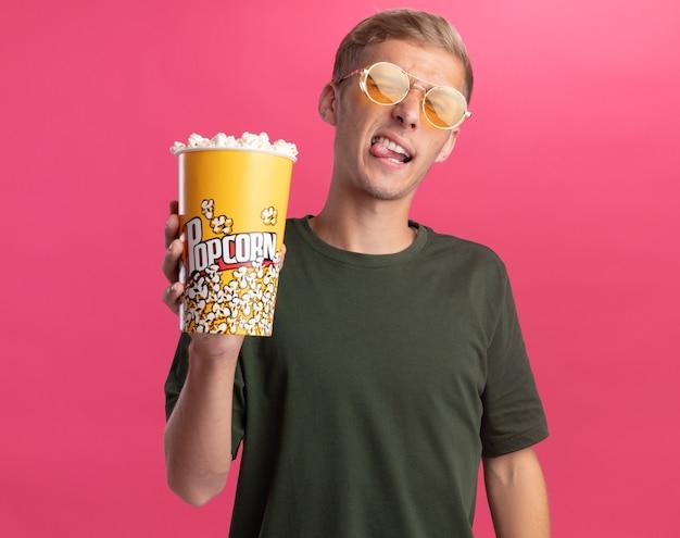 ピンクの壁に分離された舌を示すポップコーンのバケツを保持している緑のシャツと眼鏡を身に着けているうれしそうな若いハンサムな男