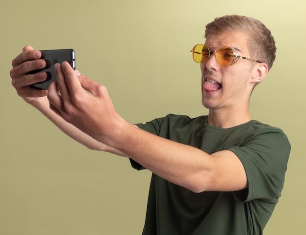 舌を示す眼鏡と緑のシャツを着て、オリーブグリーンの壁に隔離されたselfieを取るうれしそうな若いハンサムな男