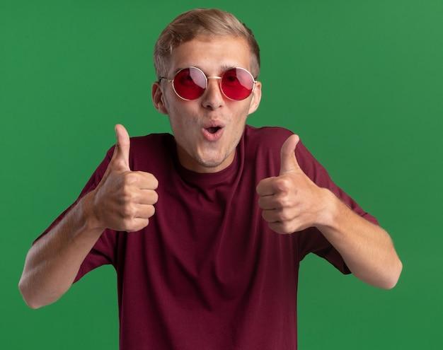 빨간 셔츠와 녹색 벽에 고립 엄지 손가락을 보여주는 안경을 쓰고 즐거운 젊은 잘 생긴 남자