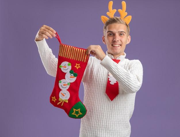 紫色の背景に分離されたカメラを見てクリスマスの靴下を保持しているトナカイの角のヘッドバンドとサンタクロースのネクタイを身に着けているうれしそうな若いハンサムな男