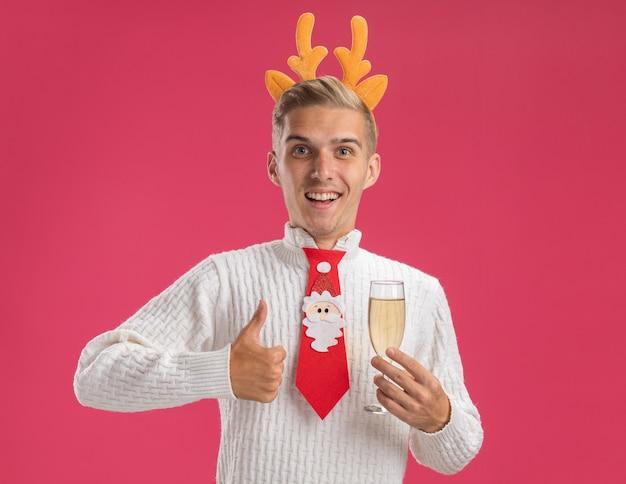 순록 뿔 머리띠와 산타 클로스 넥타이를 입고 즐거운 젊은 잘 생긴 남자가 분홍색 배경에 고립 엄지 손가락을 보여주는 카메라를보고 샴페인 잔을 들고