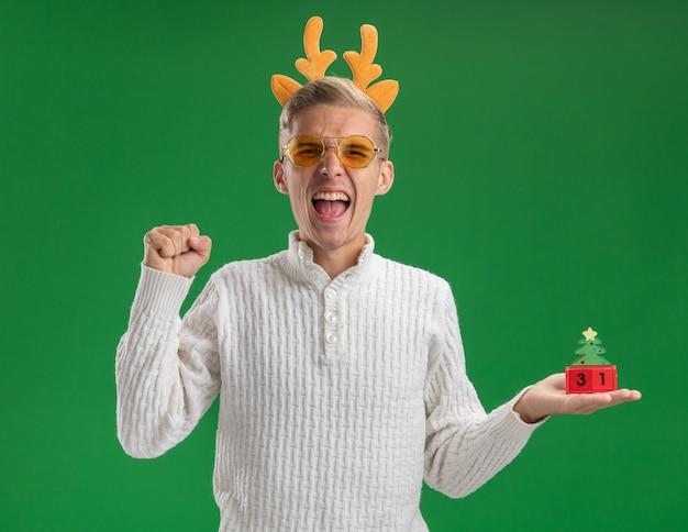 緑の背景に分離されたはいジェスチャーを行うカメラを見て日付とクリスマスツリーのおもちゃを保持しているメガネとトナカイの角のヘッドバンドを身に着けているうれしそうな若いハンサムな男