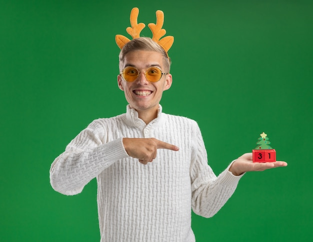 Joyful young handsome guy wearing reindeer antlers headband with glasses holding and pointing at christmas tree toy with date looking at camera isolated on green background