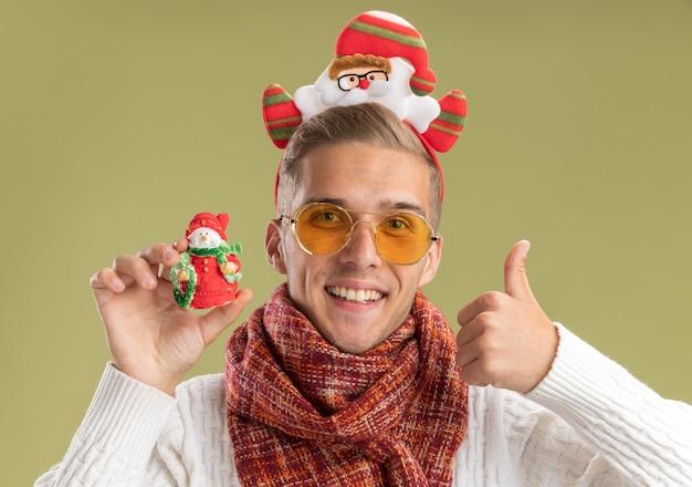 サンタクロースのヘッドバンドとスカーフを身に着けているうれしそうな若いハンサムな男は、オリーブグリーンの背景で隔離の親指を示す雪だるまのクリスマス飾りを保持しているカメラを見て