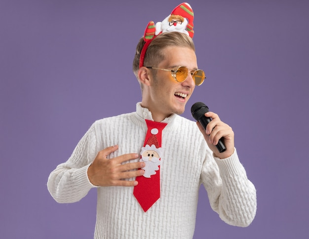 Joyful young handsome guy wearing santa claus headband and tie with glasses holding microphone keeping hand on chest looking at side singing isolated on purple wall