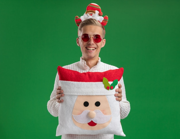 Joyful young handsome guy wearing santa claus headband with glasses holding santa claus pillow looking at camera laughing isolated on green background