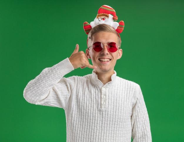 녹색 배경에 고립 된 전화 제스처를 하 고 카메라를보고 안경 산타 클로스 머리 띠를 입고 즐거운 젊은 잘 생긴 남자