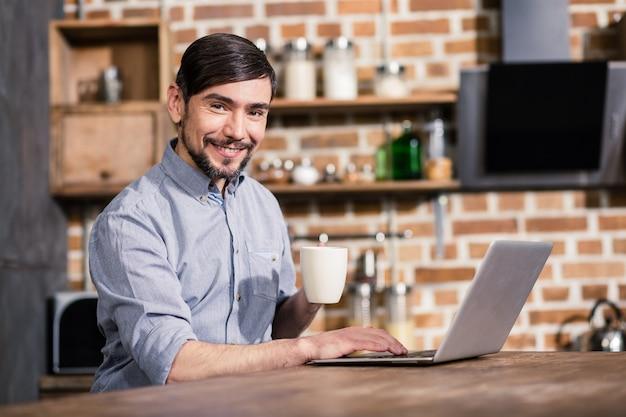Радостный молодой красавец пьет кофе во время работы в интернете