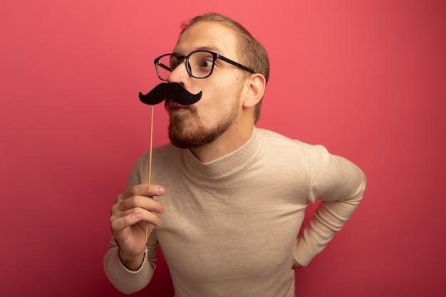 ピンクの壁の上に立って驚いて驚いた棒に面白い口ひげを持っているベージュのタートルネックとメガネのうれしそうな若いハンサムな男