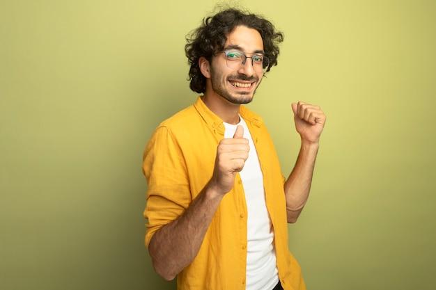 Gioioso giovane uomo bello con gli occhiali in piedi in vista di profilo guardando la parte anteriore che punta a se stesso isolato sulla parete verde oliva
