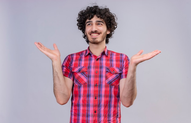 A joyful young handsome man with curly hair in checked shirt opening hands