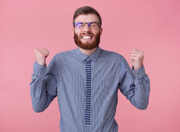 Joyful young handsome red bearded man with glasses and a striped shirt, stands over pink background, clenched his fists, broadly smiling and absolutely happy - he won the lottery!