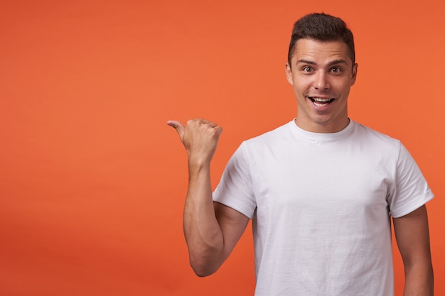 Gioioso giovane maschio bello dai capelli corti bruna guardando felicemente la fotocamera con un ampio sorriso mentre sfoglia da parte con la mano alzata, isolata su sfondo arancione