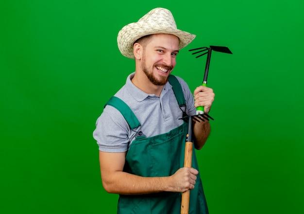 Радостный молодой красивый славянский садовник в униформе и шляпе смотрит с граблями и граблями