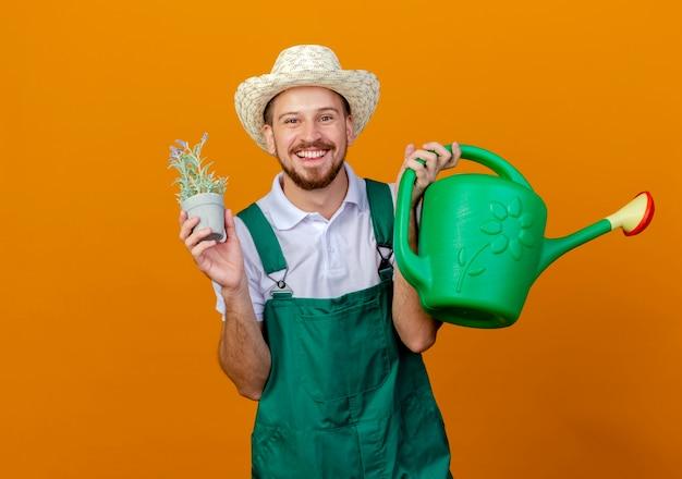 Gioioso giovane giardiniere slavo bello in uniforme e cappello che tiene annaffiatoio e vaso di fiori che sembrano isolati