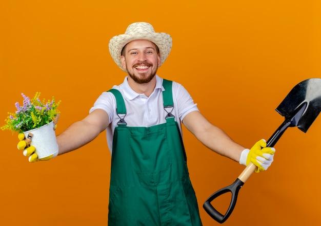 Gioioso giovane giardiniere slavo bello in uniforme che indossa cappello e guanti da giardinaggio allungando vanga e vaso di fiori isolato