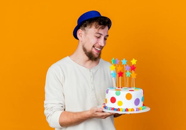 즐거운 젊은 잘 생긴 슬라브 파티 남자 파티 모자를 쓰고 복사 공간이 오렌지 배경에 고립 된 별과 생일 케이크를보고