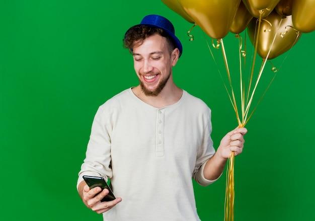 風船と携帯電話を保持しているパーティーハットを身に着けているうれしそうな若いハンサムなスラブ党の男は、コピースペースで緑の背景に分離された電話を見て